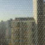Bubble wrap covering a window for insulation with a city skyline in the background