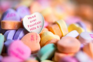 Pile of multicolored candy hearts with a white heart that says Head over Fountain Hills for you in the forefront