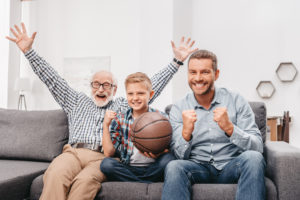 Little boy on couch with grandfather and father, cheering for a basketball game and holding a basketball ball