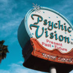 Blue sky with a sign advertising for Psychic Vision Present Past Future