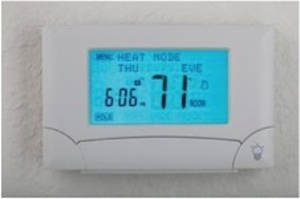 Programmable thermostat with backlit digital screen.